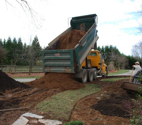March 16. Perhaps the scariest part of the day was watching 11 yards of screened top soil (clay) being dumped to build up berms on either side of the path. The tractor moved it all into place, but my formerly green grass path was history.